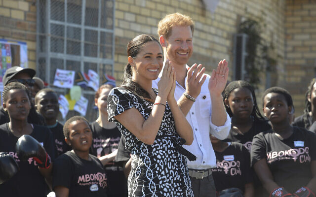 Britain's Prince Harry and Meghan, Duchess of Sussex, greet youths on a visit to the Nyanga Methodist Church in Cape Town, South Africa, September 23, 2019. (Courtney Africa/Pool via AP, File)