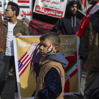 "A child with the colors of the Iraqi flag on his face walks past a poster with Arabic that reads ""leave us live in peace,"" during the ongoing protests in Tahrir square, Baghdad, Iraq, Friday, Jan. 10, 2020. (AP Photo/Nasser Nasser)"