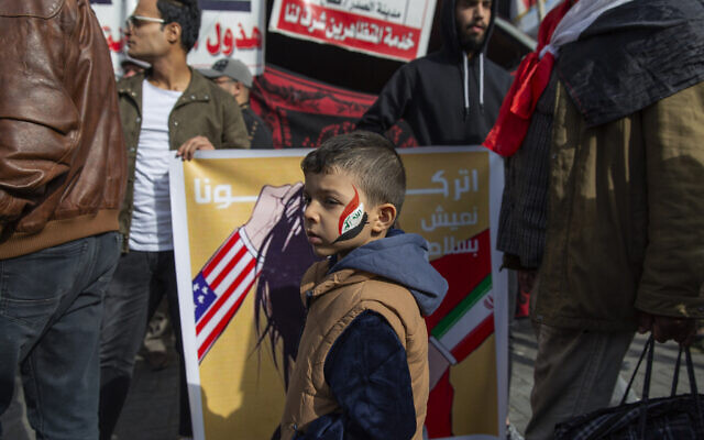 """A child with the colors of the Iraqi flag on his face walks past a poster with Arabic that reads """"leave us live in peace,"""" during the ongoing protests in Tahrir square, Baghdad, Iraq, Friday, Jan. 10, 2020. (AP Photo/Nasser Nasser)"""