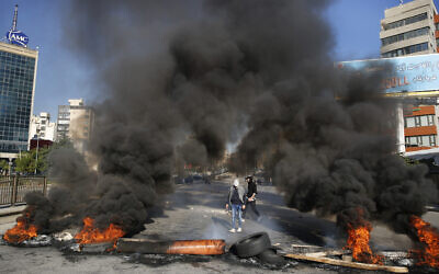 Anti-government protesters burn tires during ongoing protests after weeks of calm in Beirut, Lebanon, January 14, 2020. (Hussein Malla/AP)