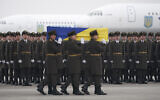 Honor guards carry a coffin of one of the eleven Ukrainian victims of the Ukrainian 737-800 plane that crashed on the outskirts of Tehran, during a memorial ceremony at Borispil international airport outside Kyiv, Ukraine, January 19, 2020. (Ukrainian Presidential Press Office via AP)
