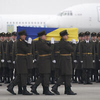 Honor guards carry a coffin of one of the eleven Ukrainian victims of the Ukrainian 737-800 plane that was shot down in error by Iran on the outskirts of Tehran, during a memorial ceremony at Borispil international airport outside Kyiv, Ukraine, January 19, 2020. (Ukrainian Presidential Press Office via AP)