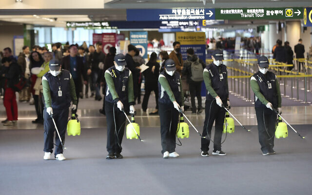 Workers spray antiseptic solution on the arrival lobby amid rising public concerns over the possible spread of a new coronavirus at Incheon International Airport in Incheon, South Korea, January 21, 2020. (Suh Myung-geon/Yonhap via AP)