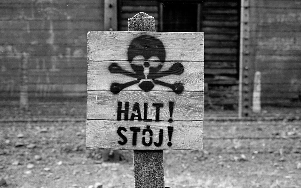 A wooden sign with the word STOP stands in front of what was an electric barbed wire fence inside the former Nazi death camp of Auschwitz I, in Oswiecim, Poland, December 8, 2019. (Markus Schreiber/AP)