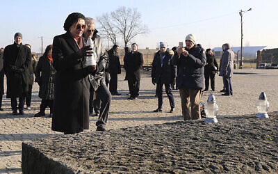 In this image provided by the US Consulate General in Krakow, US House Speaker Nancy Pelosi places a memorial light on the monument to some 1.1 million victims of the World War II Nazi death camp of Auschwitz-Birkenau during a visit to the site of the former camp just days before the 75th anniversary of its 1945 liberation by the Soviet troops, at the Auschwitz-Birkenau Museum, in southern Poland, on Tuesday, Jan. 21, 2020. (US Consulate General in Krakow via AP)