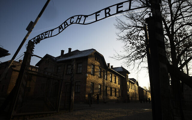 The sun lights the buildings behind the entrance of the former Nazi death camp of Auschwitz-Birkenau in Oswiecim, Poland; December 6, 2019. (Markus Schreiber/AP)