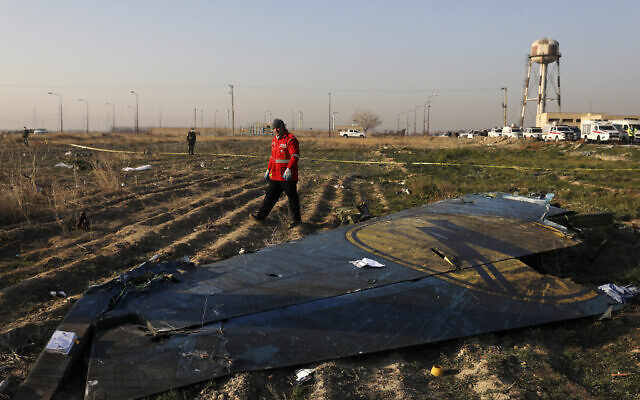 In this January 8, 2020, file photo a rescue worker searches the scene where a Ukrainian plane crashed in Shahedshahr southwest of the capital Tehran, Iran. (AP Photo/Ebrahim Noroozi, File)
