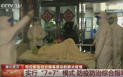 In this Thursday, Jan. 23, 2020, image from China's CCTV video, a patient is carried on a stretcher to an ambulance by medical workers in protective suits in Wuhan, China.  (CCTV via AP)