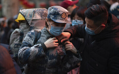 In this photo taken January 24, 2020 and released by Xinhua News Agency, a military medic from the Air Force Medical University prepares to leave for Wuhan from Xi'an, capital of northwestern China's Shaanxi Province.(Zhang Haopeng/Xinhua via AP)