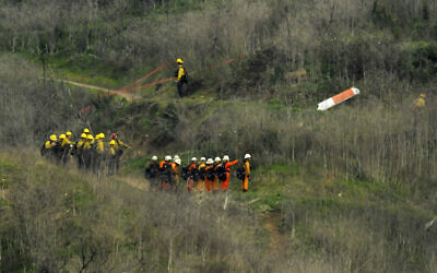 Firefighters work the scene of a helicopter crash where former NBA star Kobe Bryant died, January 26, 2020, in Calabasas, Calif. (AP Photo/Mark J. Terrill)