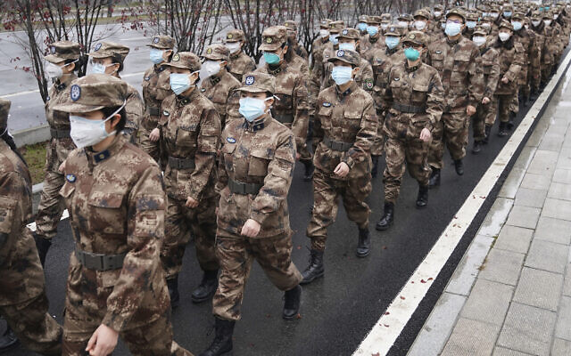 In this January 26, 2020, photo released by Xinhua News Agency, members of a military medical team head for Wuhan Jinyintan Hospital in Wuhan, central China's Hubei province. (Cheng Min/Xinhua via AP)