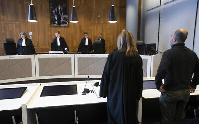 Dutch-Palestinian man Ismail Zeyada, originally from the Gaza Strip, right, and his lawyer Liesbeth Zegveld, rise as judges enter The Hague District Court, Netherlands, January 29, 2020. (Peter Dejong/AP)