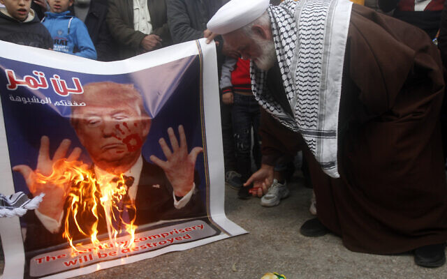 """A Palestinian cleric burns a banner that shows a portrait of the U.S. President Donald Trump with Arabic words that read:""""Your suspicious deal will not pass,"""" during a protest against the White House plan for ending the Israeli-Palestinian conflict,  at Rashidiyeh Palestinian refugee camp, southern Lebanon on January 29, 2020.  (AP/Mohammed Zaatari)"""