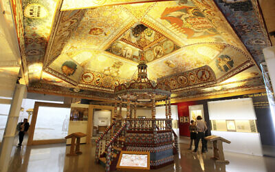 People walk through a wooden 17th century synagogue once located in Gwozdziec, a formerly Polish town now in Ukraine, at the POLIN Museum of the History of Polish Jew in Warsaw, Poland, October 21, 2014. (Czarek Sokolowski/Associated Press)