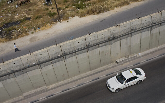 Illustrative: A Palestinian man walks along Israel's security barrier, in the West Bank town of Aram, as a taxi drives in the East Jerusalem neighborhood of Beit Hanina, May 24, 2011.  (AP Photo/Bernat Armangue)
