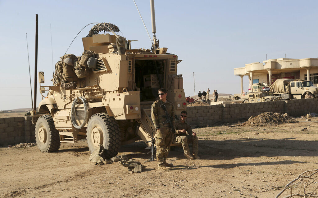 US Army soldiers stand outside their armored vehicle on a joint base with Iraqi army south of Mosul, Iraq, February 23, 2017. (Khalid Mohammed/AP/File)