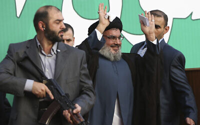 Hezbollah leader Sheik Hassan Nasrallah, center, escorted by his bodyguards, waves to a crowd of tens of thousands of supporters during a rally in a southern suburb of Beirut, Lebanon, September 17, 2012. AP Photo/Hussein Malla, File)