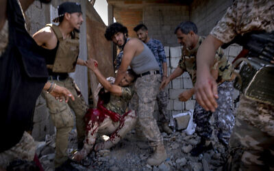 A mortally wounded fighter of the 'Shelba' unit, allied with the UN-supported Libyan government, is moved by comrades after being shot at the Salah-addin neighborhood front line in Tripoli, Libya on September 7, 2019. (AP Photo/Ricard Garcia Vilanova)