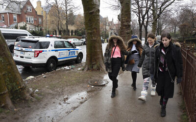 Jewish girls walk by a police car stationed in the Crown Heights neighborhood, Monday, Dec. 30, 2019 in the Brooklyn borough of New York. Police have increased patrols in the area following anti-Semitic attacks in the city and on an attack of a Hanukkah celebration in Monsey, N.Y. (AP Photo/Mark Lennihan)