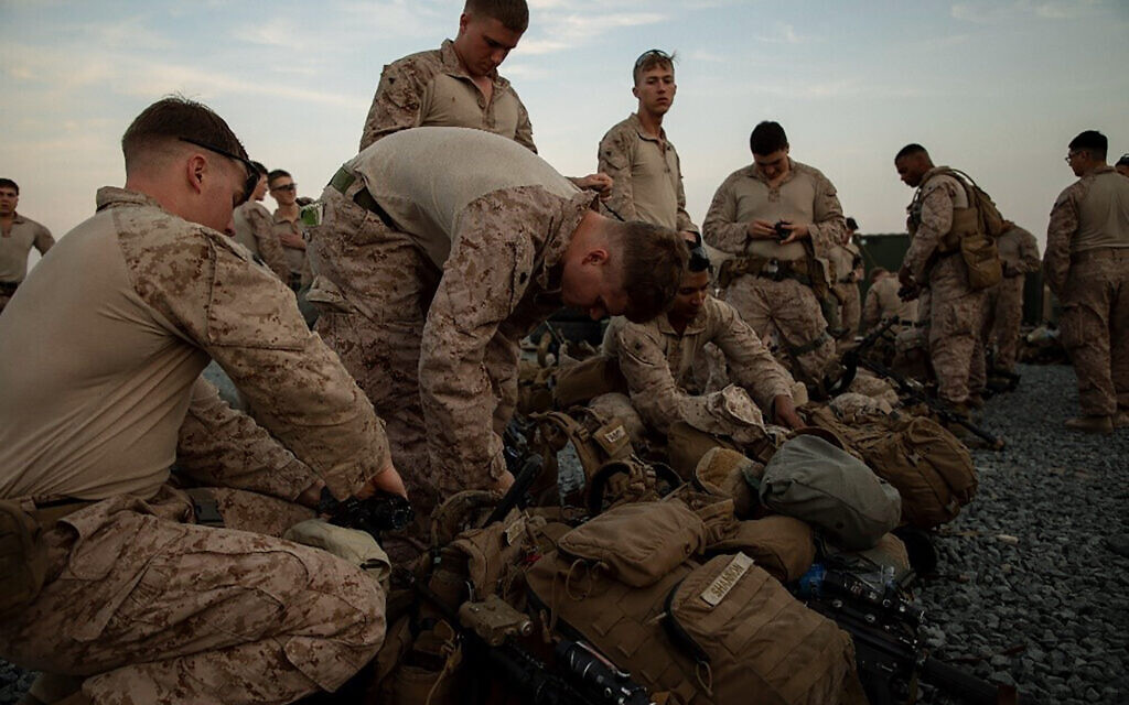 In this photo provided by U.S. Department of Defense, U.S. Marines assigned to Special Purpose Marine Air-Ground Task Force-Crisis Response-Central Command (SPMAGTF-CR-CC) 19.2, prepare to deploy from Kuwait in support of a crisis response mission, Tuesday, Dec. 31, 2019. (U.S. Marine Corps photos by Sgt. Robert G. Gavaldon via AP)