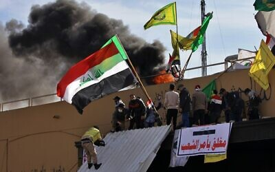 Pro-Iranian militiamen and their supporters set a fire during a sit-in in front of the US embassy in Baghdad, Iraq, January 1, 2020. (AP Photo/Khalid Mohammed)
