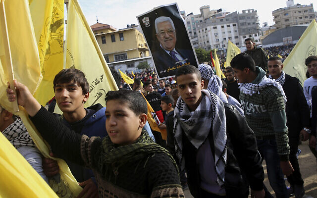 Palestinian Fatah supporters hold a portrait of Palestinian Authority President Mahmoud Abbas during a celebration marking the 55th anniversary of the Fatah movement, in Gaza City, Wednesday, Jan. 1, 2020. (AP Photo/Adel Hana)