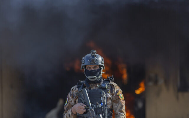 An Iraqi soldier stands guard in front of smoke rising from a fire set by pro-Iranian militiamen and their supporters in the US embassy compound, Baghdad, Iraq, Wednesday, January 1, 2020. (AP Photo/Nasser Nasser)