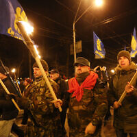 Activists of various nationalist parties carry torches during a rally in Kyiv, Ukraine on January 1, 2020. (AP Photo/Efrem Lukatsky)