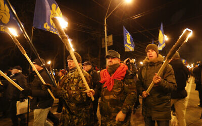 Activists of various nationalist parties carry torches during a rally in Kyiv, Ukraine, Wednesday, Jan. 1, 2020. The rally was organized to mark the birth anniversary of Stepan Bandera, founder of a rebel army that fought against the Soviet regime and who was assassinated in Germany in 1959. (AP Photo/Efrem Lukatsky)