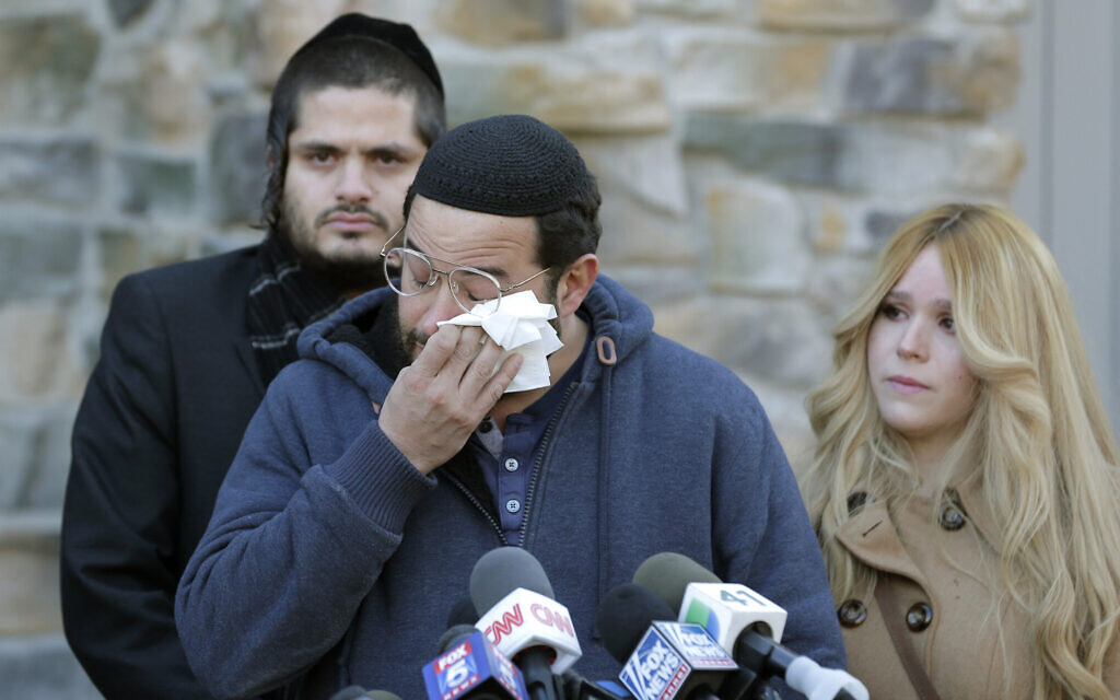 Surrounded by family, David Neumann, center, wipes his eyes as he speaks to reporters in New City, New York, Thursday, Jan. 2, 2020, about his father, Josef Neumann, who was critically injured in an attack on a Hanukkah celebration (AP Photo/Seth Wenig)