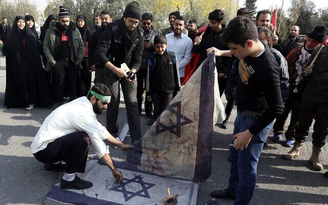 Protesters burn representations of Israeli flag during a demonstration over the US airstrike in Iraq that killed Iranian Revolutionary Guard Gen. Qassem Soleimani, in Tehran, Iran, Jan. 3, 2020 (AP Photo/Vahid Salemi)