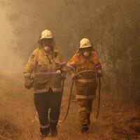 Firefighters drag their water hose after putting out a spot fire near Moruya, Australia, Jan. 4, 2020. (AP Photo/Rick Rycroft)