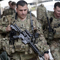 US Army soldiers with their gear head to an awaiting bus on January 4, 2020 at Fort Bragg, NC, as troops from the 82nd Airborne are deployed to the Middle East as reinforcements in the volatile aftermath of the killing of Iranian Gen. Qassem Soleimani. (AP Photo/Chris Seward)