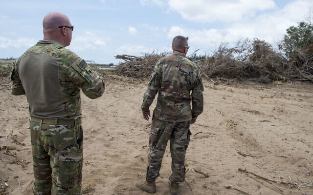 In this photo taken February 24, 2018 and released by the US Air Force, US servicemen look at trees that are being cleared during a battlefield circulation site visit at Camp Simba, Manda Bay, Kenya. (Staff Sgt. Timothy Moore/U.S. Air Force via AP)