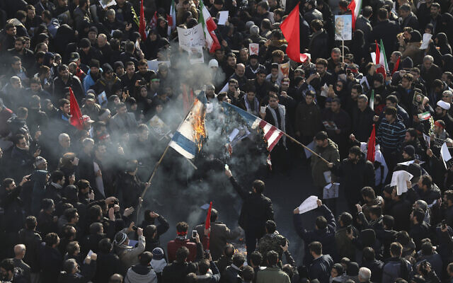 Mourners burn flags of the US and Israel during a funeral ceremony for Iranian Gen. Qassem Soleimani and his comrades, who were killed in Iraq in a US drone strike on Friday, at the Enqelab-e-Eslami (Islamic Revolution) square in Tehran, Iran,  Jan. 6, 2020. (AP Photo/Ebrahim Noroozi)