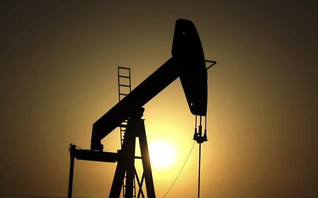 In this June 8, 2011 file photo, sun sets behind an oil pump in the desert oil fields of Sakhir, Bahrain (AP Photo/Hasan Jamali, File)