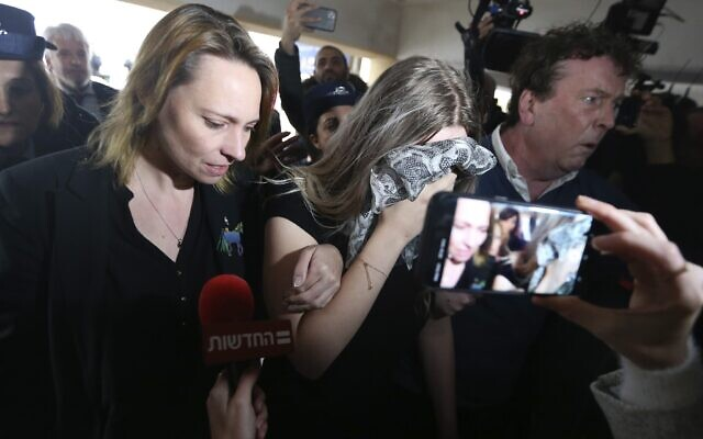A 19 year-old British woman, center, who was found guilty of making up claims she was raped by up to 12 Israelis arrives at Famagusta District Court for sentencing on January 7, 2020 (AP Photo/Petros Karadjias)