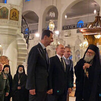 Russian President Vladimir Putin, third right, and Syrian President Bashar Assad, center, visiting an Orthodox cathedral for Christmas, in Damascus, Syria, January 7, 2020. (Syrian Presidency via AP)