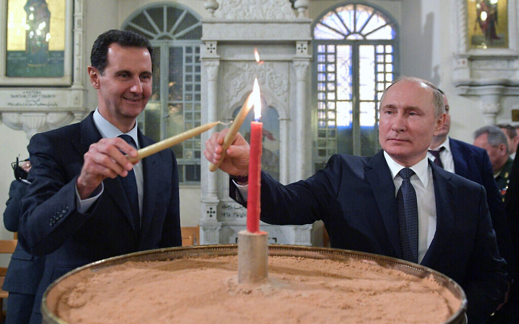 Russian President Vladimir Putin, right, and Syrian President Bashar Assad light candles while visiting an orthodox cathedral for Christmas, in Damascus, Syria, January 7, 2020. (Alexei Druzhinin, Sputnik, Kremlin Pool Photo via AP)