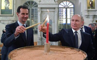 Russian President Vladimir Putin, right, and Syrian President Bashar Assad light candles while visiting an orthodox cathedral for Christmas, in Damascus, Syria, January 7, 2020. (Alexei Druzhinin, Sputnik, Kremlin Pool Photo via AP)