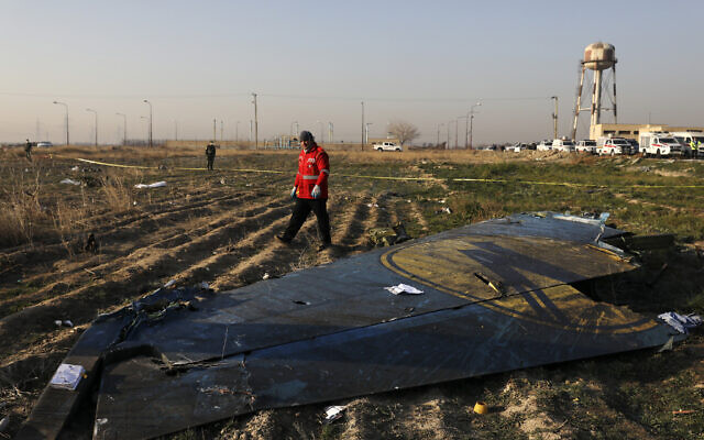 In this Wednesday, Jan. 8, 2020 photo a rescue worker searches the scene where a Ukrainian plane crashed in Shahedshahr southwest of the capital Tehran, Iran. (AP/Ebrahim Noroozi)