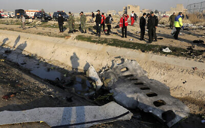 Debris is seen from an Ukrainian plane which crashed as authorities work at the scene in Shahedshahr, southwest of the capital Tehran, Iran, Wednesday, Jan. 8, 2020 (AP Photo/Ebrahim Noroozi)