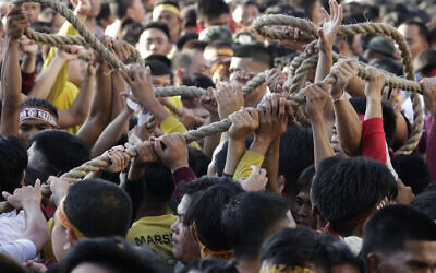 Filipino Roman Catholic devotees jostle to get the rope that pulls the carriage of the Black Nazarene during a raucous procession to celebrate its feast day, Jan. 9, 2020, in Manila, Philippines (AP Photo/Aaron Favila)