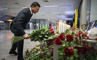 Ukrainian President Volodymyr Zelensky lays flowers at a memorial of the flight crew members of the Ukrainian 737-800 plane that crashed on the outskirts of Tehran, at Borispil international airport outside in Kyiv, Ukraine, January 9, 2020. (Ukrainian Presidential Press Office via AP)
