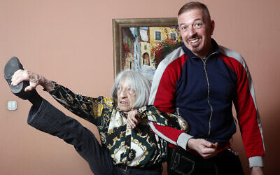 Agnes Keleti, former Olympic gold medal winning gymnast, demonstrates her flexibility as she poses for a photo with her son Rafael at her apartment in Budapest, Hungary on January 8, 2020. (AP Photo/Laszlo Balogh)