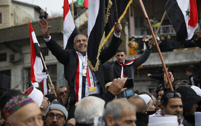 Druze men carry Sidqi al-Maqt, left, and Amal Abu Saleh as they wave Syrian flags upon their release from Israeli prison, in the Golan Heights town of Majdal Shams on the border with Syria, January 10, 2020. (AP Photo/Ariel Schalit)