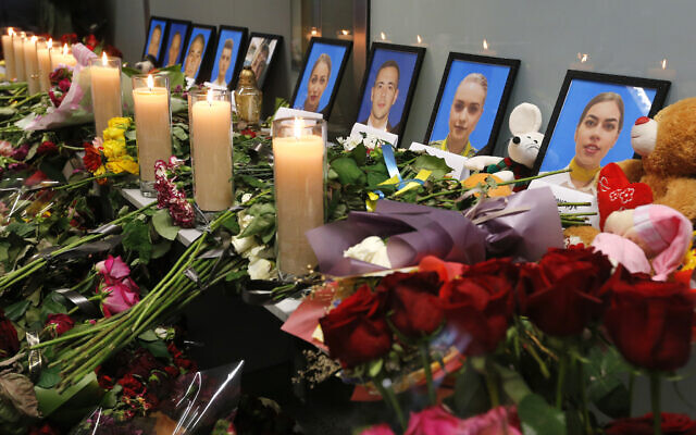Flowers and candles are placed in front of portraits of the flight crew members of the Ukrainian 737-800 plane that crashed on the outskirts of Tehran, at a memorial inside Borispil international airport outside Kyiv, Ukraine, January 11, 2020. (AP Photo/Efrem Lukatsky)