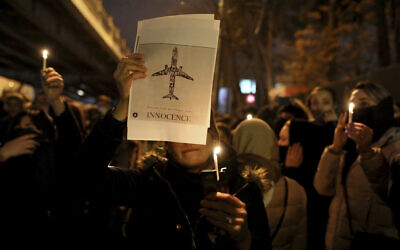 People gather for a candlelight vigil to remember the victims of the Ukraine plane crash, at the gate of Amri Kabir University where some of the victims of the crash were former students, in Tehran, Iran, January 11, 2020. (AP/Ebrahim Noroozi)
