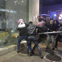 Anti-government protesters smash a bank widow, during ongoing protests against the Lebanese central bank's governor and against the deepening financial crisis, at Hamra trade street, in Beirut, Lebanon, January 14, 2020. (Hussein Malla/AP)