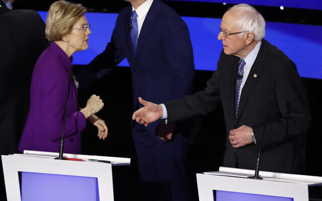 Democratic presidential candidate Sen. Elizabeth Warren, Democrat-Massachusetts, left and Sen. Bernie Sanders, Independent-Vermont talk after a Democratic presidential primary debate hosted by CNN and the Des Moines Register in Des Moines, Iowa, January 14, 2020. (AP Photo/Patrick Semansky)